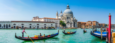 canals: Beautiful view of traditional Gondolas on Canal Grande with historic Basilica di Santa Maria della Salute in the background on a sunny day in Venice, Italy Stock Photo