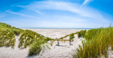 Hermosa tranquilo paisaje de dunas con banco idílico con vistas al mar del Norte alemán y una larga playa en la isla de Amrum, Schleswig-Holstein, Alemania