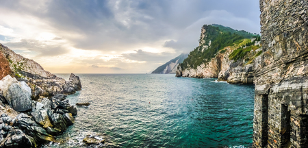 rough sea: Beautiful view on the wild Ligurian Coast with an impressive shoreline, rough sea and dramatic cloudscape from the famous Cathedral of St. Peter in the town of Porto Venere at sunset, La Spezia, Italy Stock Photo