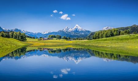 Panoramic view of idyllic summer landscape in the Alps with clear mountain lake and fresh green mountain pastures in the background. Stock Photo