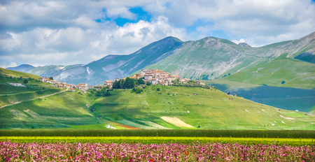 sibillini: Historic city of Castelluccio di Norcia with beautiful summer landscape at Piano Grande Great Plain mountain plateau in the Apennine Mountains, Umbria, Italy