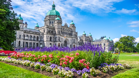 victoria: Beautiful view of historic parliament building in the citycenter of Victoria with colorful flowers on a sunny day, Vancouver Island, British Columbia, Canada