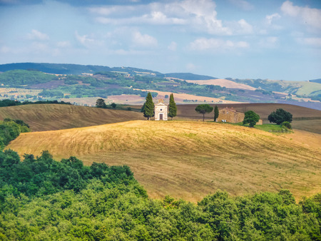 val dorcia: Panoramic view of beautiful Tuscany landscape with rolling hills and golden harvest fields and famous Cappella della Madonna di Vitaleta in Val dOrcia, province of Siena, Italy Stock Photo
