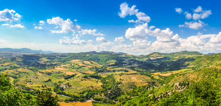 italy landscape: Panoramic view of beautiful tuscan landscape with rolling hills, golden harvest fields, green wine gardens and an old cemetery from top of the ancient town of Assisi, Umbria, Italy