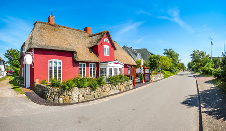 Beautiful idyllic and traditional thatched house in a typical german north sea village on a sunny day