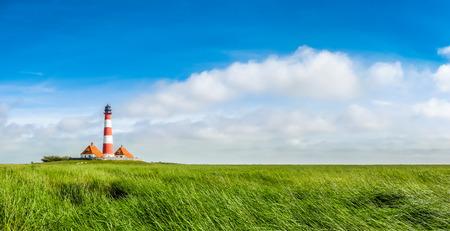 cielo azul: Hermoso paisaje con famoso faro Westerheversand en el Mar del Norte en Nordfriesland, en Schleswig-Holstein, Alemania Foto de archivo