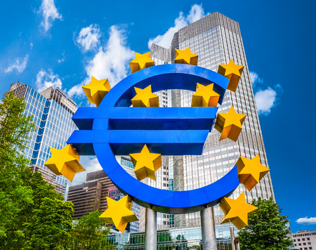 Euro sign at European Central Bank headquarters in Frankfurt, Germany with dark dramatic clouds symbolizing a financial crisis