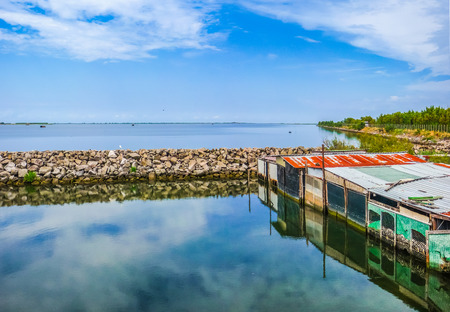 estuary: Beautiful view of tranquil seascape with colorful shanties in the Delta del Po national park region on a sunny day, Venetian Lagoon, Adriatic Sea, Italy Stock Photo