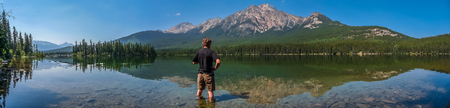 banff: Beautiful panoramic view of lonely man standing in Pyramid Lake with great mountain landscape in the background, Jasper National Park, Alberta, Canada