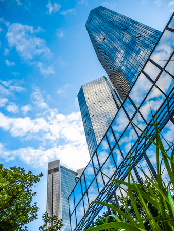 frankfurt stock exchange: Bottom view of modern skyscrapers in business district against blue sky
