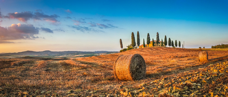 val d'orcia: Panoramic view of beautiful Tuscany landscape with traditional farm house and hay bales in golden evening light, Val dOrcia, Italy