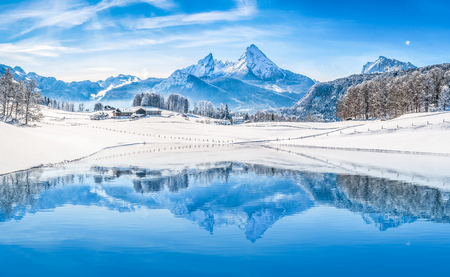 winter day: Winter wonderland scenery in the Alps with snowy mountain summits reflecting in crystal clear mountain lake on a cold sunny day with blue sky and clouds
