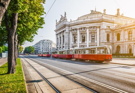 Famoso Wiener Ringstrasse con Burgtheater histórico y tranvía eléctrico tradicional rojo al amanecer con efecto de filtro de estilo vintage retro en Viena, Austria Foto de archivo