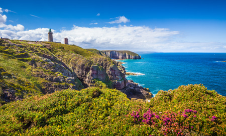 Panoramic view of scenic coastal landscape with traditional lighthouse at famous Cap Frehel peninsula, Bretagne, northern France