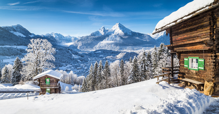 chalets: Winter wonderland mountain scenery in the Alps with traditional mountain chalets on a cold sunny day with blue sky and clouds
