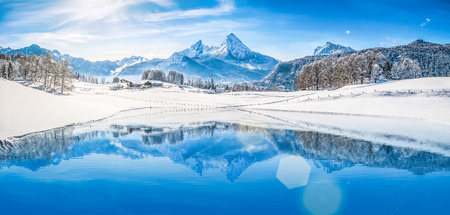 reflection: Panoramic view of beautiful white winter wonderland scenery in the Alps with snowy mountain summits reflecting in crystal clear mountain lake on a cold sunny day with blue sky and clouds