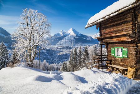푸른 하늘과 구름과 차가운 화창한 날에 전통적인 산 샬레와 알프스에 겨울 원더 랜드 산의 경치