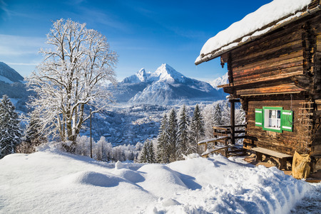 outdoor scenery: Winter wonderland mountain scenery in the Alps with traditional mountain chalet on a cold sunny day with blue sky and clouds