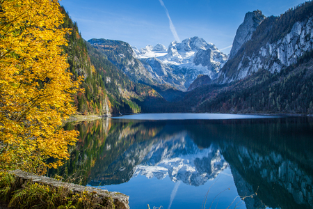crystal clear: Beautiful view of idyllic colorful autumn scenery with Dachstein mountain summit reflecting in crystal clear Gosausee mountain lake in fall, Salzkammergut region, Upper Austria, Austria Stock Photo