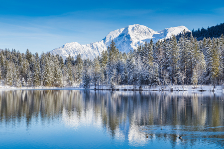 Idyllic winter wonderland with crystal clear mountain lake in the Alps on a cold sunny day