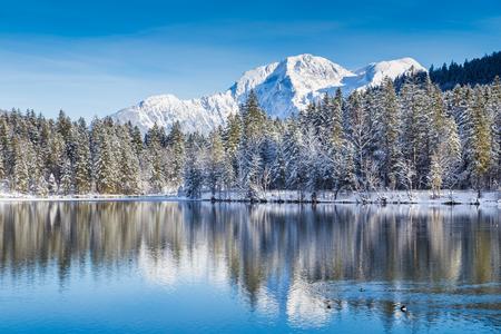 Idyllische winter wonderland met kristalhelder bergmeer in de Alpen op een koude zonnige dag Stockfoto