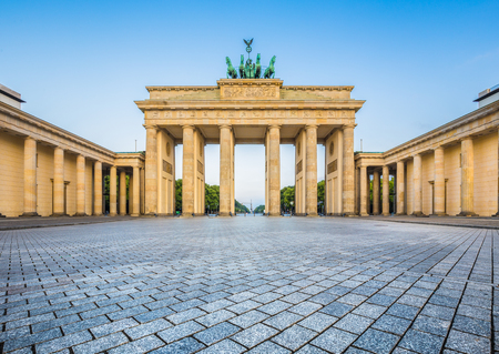 Famous Brandenburg Gate, one of the best-known landmarks and national symbols of Germany, in beautiful golden morning light at sunrise, Berlin, Germany
