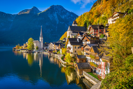 sunrise mountain: Scenic picture-postcard view of famous Hallstatt mountain village with Hallstatter See in the Austrian Alps in beautiful golden morning light in fall, region of Salzkammergut, Austria Stock Photo
