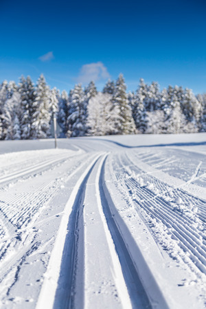 Close-up view of empty cross-country skiing track in beautiful winter wonderland scenery