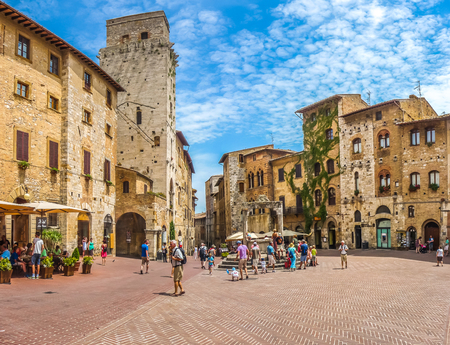 Panoramablick auf die berühmte Piazza della Cisterna in der historischen Stadt San Gimignano an einem sonnigen Tag, Toskana, Italien