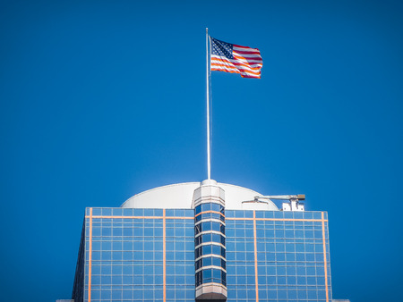 wallstreet: American flag waving on top of a modern skyscraper high in the air on a sunny day against the blue sky Stock Photo