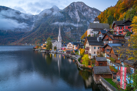 Scenic picture-postcard view of famous historic Hallstatt mountain village with Hallstatter See in the Austrian Alps in twilight during blue hour at dawn in fall, region of Salzkammergut, Austria