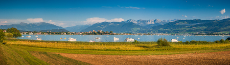 sg: Beautiful panoramic view of boats lying in Lake Zurich with the historic town of Rapperswil in the background in golden evening light at sunset in summer, Rapperswil-Jona, canton of St. Gallen, Switzerland