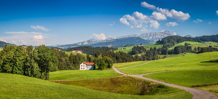 Beautiful view of idyllic mountain scenery in the Alps with green meadows and famous Saentis summit in the background on a sunny day with blue sky and clouds in summer, Appenzellerland, Switzerland 免版税图像