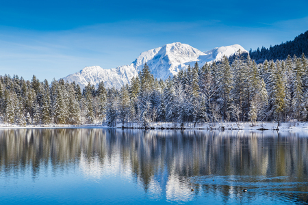 german swiss: Idyllic winter wonderland with crystal clear mountain lake in the Alps on a cold sunny day