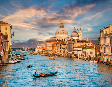 Beautiful view of traditional Gondola on famous Canal Grande with Basilica di Santa Maria della Salute at sunset in Venice, Italy
