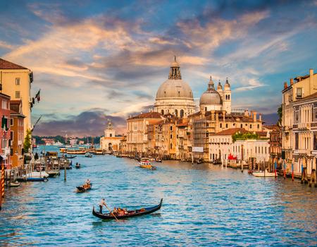 Schöne Aussicht auf traditionelle Gondel auf berühmten Canal Grande mit Basilica di Santa Maria della Salute bei Sonnenuntergang in Venedig, Italien