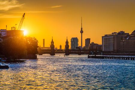 일몰 황금 저녁 빛에 강 이어지고에서 유명한 TV 타워와 Oberbaum 다리와 함께 베를린 스카이 라인의 아름 다운보기