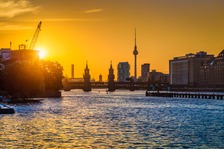 river: Beautiful view of Berlin skyline with famous TV tower and Oberbaum Bridge at river Spree in golden evening light at sunset