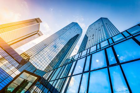 Widok z dołu nowoczesnych drapaczy chmur w dzielnicy biznesowej na zachód słońca z obiektywu pochodni efekt filtra