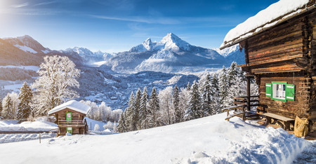 lodges: Panoramic view of beautiful winter wonderland mountain scenery in the Alps with traditional mountain chalets Stock Photo