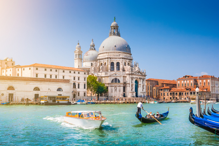 venice: Beautiful view of traditional Gondola on Canal Grande with historic Basilica di Santa Maria della Salute in the background on a sunny day in Venice, Italy