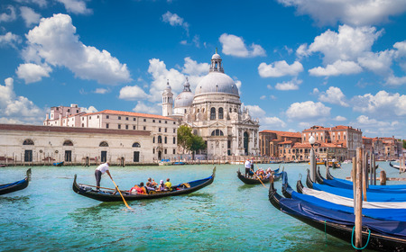 venice italy: Beautiful view of traditional Gondolas on Canal Grande with historic Basilica di Santa Maria della Salute