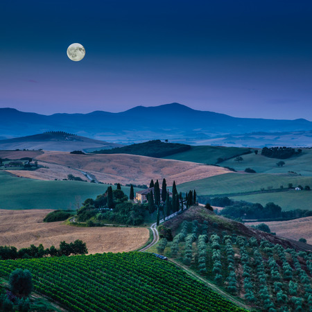 val d'orcia: Scenic Tuscany landscape with rolling hills and valleys in beautiful moonlight at dawn, Val dOrcia, Italy Stock Photo