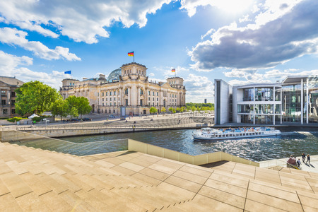 lobe: Panoramic view of Berlin government district with excursion boat on Spree river passing famous Reichstag building and Paul Lobe Haus on a sunny day with blue sky and clouds, Berlin, Germany