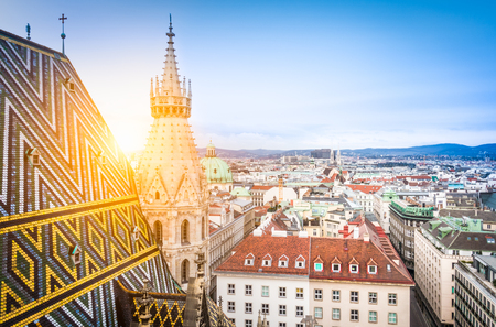 ornately: Aerial view over the rooftops of Vienna from the north tower of St. Stephens Cathedral including the cathedrals famous ornately patterned, richly colored roof created by 230,000 glazed tiles, Austria