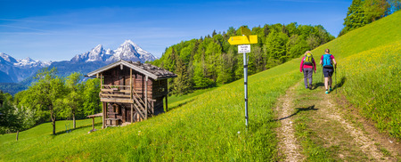 Panoramic view of idyllic mountain landscape in the Alps with hikers on hiking trail along fresh green mountain pastures, flowers and old traditional mountain lodge in springtime