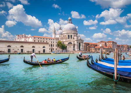basilica: Beautiful view of traditional Gondolas on Canal Grande with historic Basilica di Santa Maria della Salute in the background on a sunny day in Venice, Italy Stock Photo