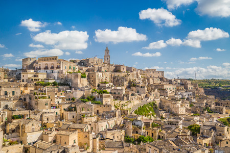 Ancient town of Sassi di Matera, European Capital of Culture 2019, in beautiful golden morning light at sunrise with blue sky and clouds, Basilicata, southern Italy