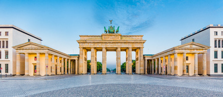quadriga: Panoramic view of famous Brandenburg Gate, one of the best-known landmarks and national symbols of Germany, in beautiful golden morning light at sunrise, Pariser Platz, Berlin, Germany