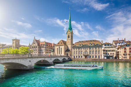 excursion: Historic city center of Zurich with famous Fraumunster Church and excursion boat on river Limmat, Canton of Zurich, Switzerland Stock Photo